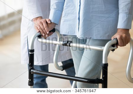 Close Up Nurse Holding Disabled Older Woman Hand On Walker