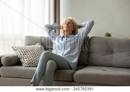 Peaceful Older Woman Sitting On Couch, Relaxing At Home