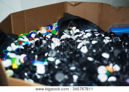 Waste Heap From Plastic Bottle Caps On Waste Sorting Station. Large Pile Of Colored Stoppers Destine