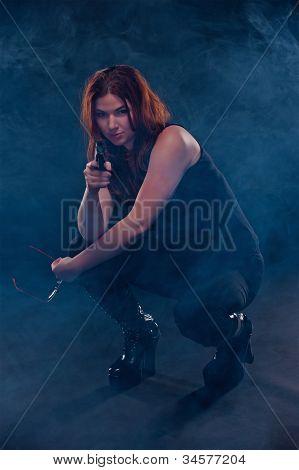 Woman crouching down aiming a gun
