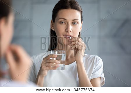 Head Shot Beautiful Woman Taking Pill, Looking In Mirror