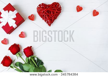 Kraft Gift Box With Beautiful White Ribbon And Red Rose, Candles In The Form Of A Heart Next To A Re