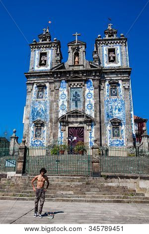 Porto, Portugal - May, 2018: Skater Practicing In Front Of The Igreja De Santo Ildefonso An Eighteen
