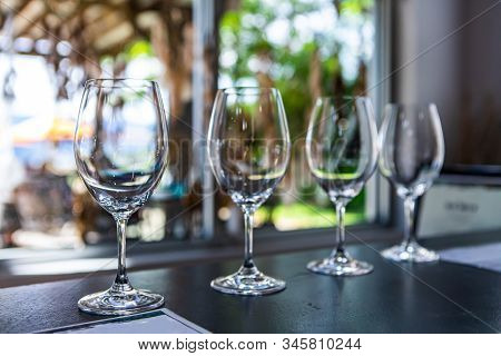 Side By Side Various Sizes Of Wine Empty Glasses On A Restaurant Table Selective Focus View, Goblets