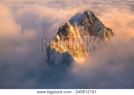 The Top Of The Mountain Runs Out Of The Inverse Cloud And Is Illuminated By The Rising Sun.