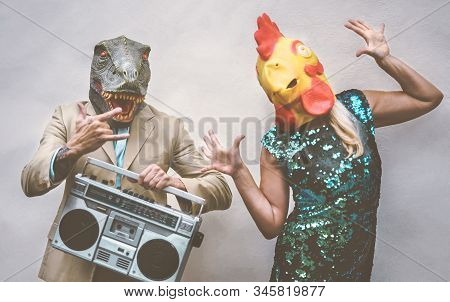 Crazy Senior Couple Wearing Chicken And T-rex Mask While Dancing Outdoor - Mature Trendy People Havi