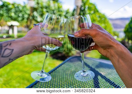 Man And Woman Hands Cheering Wine Glasses As They Sitting Against Beautiful Landscape Of Winery Vine
