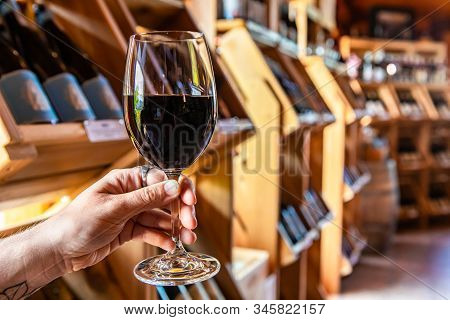 Hand Holding A Glass Of Red Wine Selective Focus View, Tasting Room Wines Bottles Display On Wooden