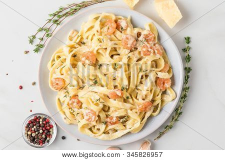 Pasta With Shrimps, Creamy Sauce, Parmesan Cheese And Thyme On A Plate. Mediterranean Fettuccine Wit