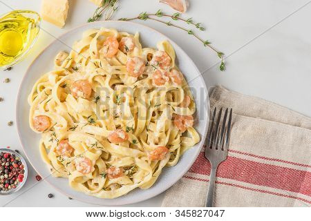 Italian Pasta Fettuccine Or Tagliatelle With Shrimps In A Creamy Sauce With Parmesan Cheese And Thym