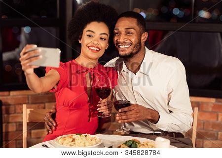Valentines Selfie. Happy African American Couple Making Self-portrait On Smartphone Holding Wine Gla