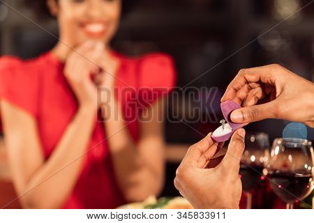 Proposal. Black Man Proposing Opening Engagement Ring Box And Asking Surprised Girlfriend To Marry H