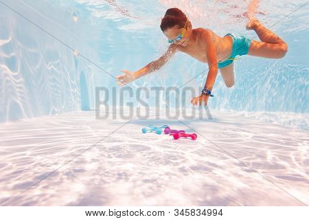 Little Boy Swim Underwater In The Pool Wearing Googles Side View Diving To Get The Toy