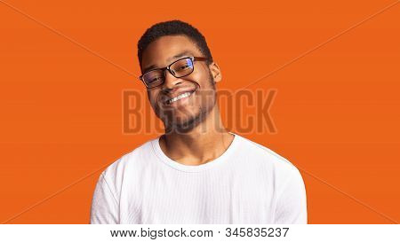 Eyewear Store. Happy Black Man In Glasses Looking At Camera Isolated Over Orange Background. Copyspa