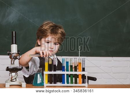 Education. Happy Smiling Pupil Drawing At The Desk. Chemistry. The Science Classroom. Lesson Plans -