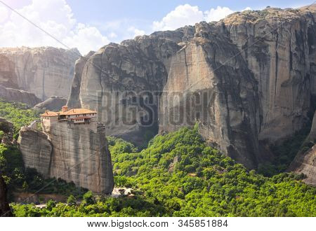 Arial view on mountains, forest and Orthodox monastery of Rousanou (nunnery St. Barbara) on  monolithic pillar in Meteora, Pindus Mountains, Thessaly, Greece, Europe