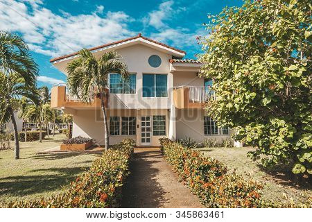 Beautiful Landscape Design In Front Of A Two-story Mansion. Palm Trees Grow In The Garden. A Hedge O