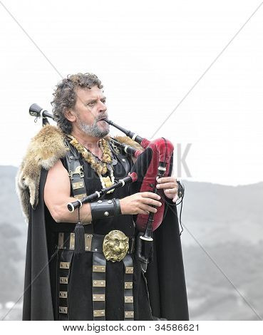 ASTURIAS, SPAIN - AUGUST 21: Celtic piper playing the bagpipes in a representation of the battle be.