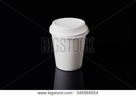 White Disposable Carboard Coffee Cup With Plastic Lid On A Black Background.