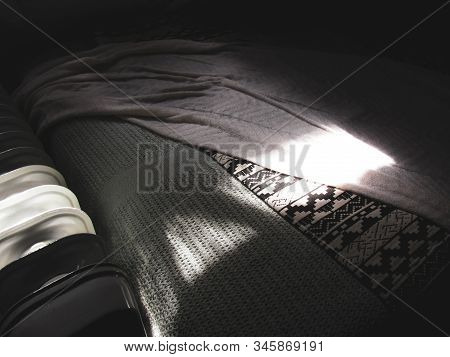 Sunlight Coming From The Bedroom Window Illuminates The Layer Of Sheets On A Comfy Bed. Suitable To