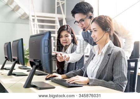 Young adult confidence with smiling supervisor teaching to his team of operator team agent with headsets and desktop computer in a call center to monitor her employee.