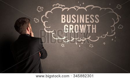 businessman drawing a cloud with BUSINESS GROWTH inscription inside, modern business concept