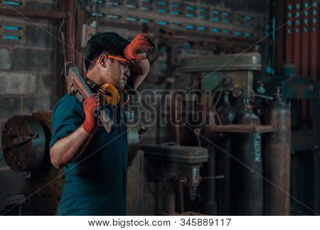 Asian Male Engineer In Repair Garage Wiping Sweat Away From His Head While Working During Long Day S