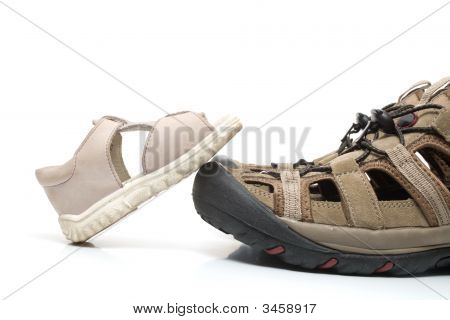 Small baby sandal stepping on huge adult shoe isolated on white background poster