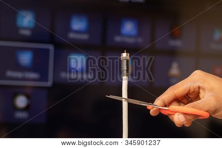 Maski, India 18, January 2020 - Hand Cutting Tv Cord In From Of The Smart Tv Showing Different Strea