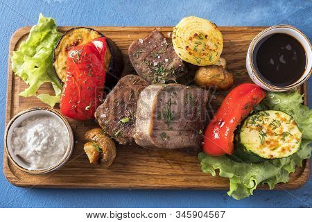 Beef Tongue On A Grill With Vegetables Served With Demiglas Sauce And Horse-radish. Top View