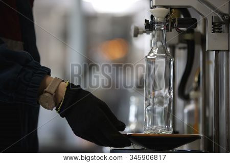 Glassworks. Hands Hold A Glass Bottle Over The Device. Quality Control Of Glass Containers