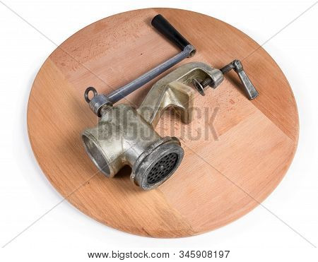 Old Hand-powered Meat Grinder Lying On The Round Wooden Serving Board On A White Background