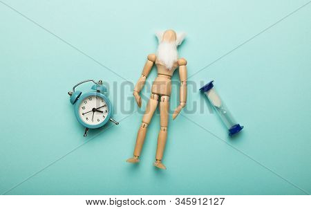 Сoncept Of Aging And Old Age (senescence). Miniature Wooden Man With Clock. Longevity Of Population.
