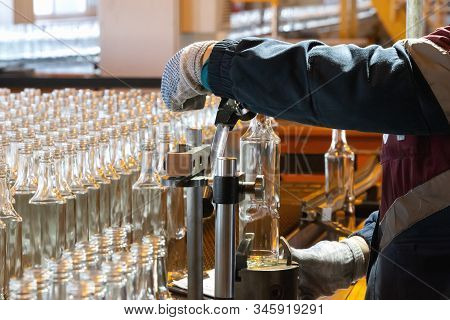 Glassworks. Glass Industry. Working Hands Hold A Glass Bottle On The Background Of A Conveyor Belt.