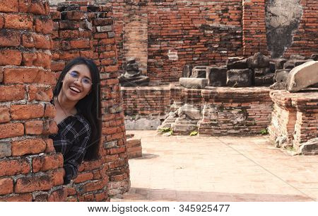 Fun Loving Young Diverse Asian Girl Hiding Behind Brick Wall And Smiling - Millennial Hipster Social
