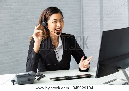 Cheerful Asian Man And Woman In Headsets Smiling And Typing On Computer Keyboard While Working In Of