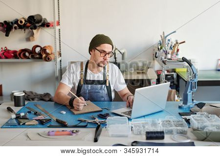 Serious young man in glasses using laptop and making notes in sketchpad while processing applications on leather goods
