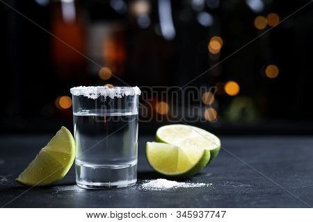 Mexican Tequila Shot With Lime Slices And Salt On Bar Counter. Space For Text