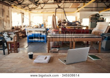 Laptop And Design Plans On A Woodworking Shop Table