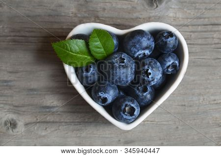 Fresh Organic Blueberries In A White Heart Shaped Bowl On Old Wooden Background.blueberry. Bilberrie