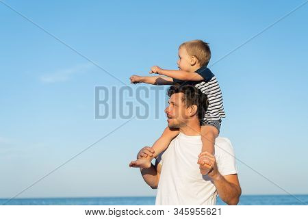 Young Caucasian Dad With Little Son Walk Warm Summer Day Along The Sea Coast. Summer Family Vacation