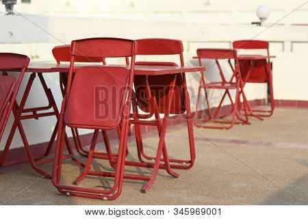 Foldable Red Table And Chair Set Placed Outdoors. Foldable Chairs, Leaning On The Table. Temporary T