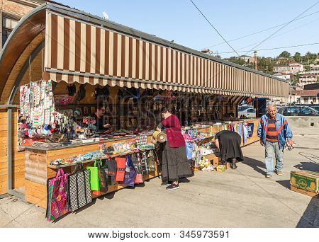 Kutaisi, Georgia, October 13, 2019 : Souvenir Seller Stands In A Covered Shop And Offers His Product