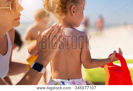 Caring Mother Apply Sunblock To The Back Of Her Little Daughter. Summer Vacation Sea Beach. Caucasia