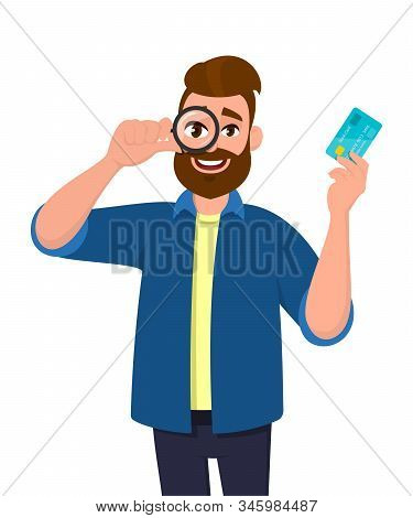 Hipster Young Man Looking Through Magnifying Glass Or Magnifier And Showing Credit, Debit Or Atm Car