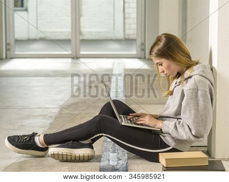 Photo Of A Young Woman Student Sitting In A Hallway With A Laptop.