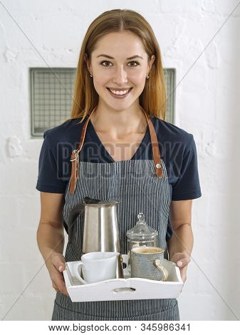 Happy And Beautiful Young Blond Woman Wearing An Apron And Serving Coffee.
