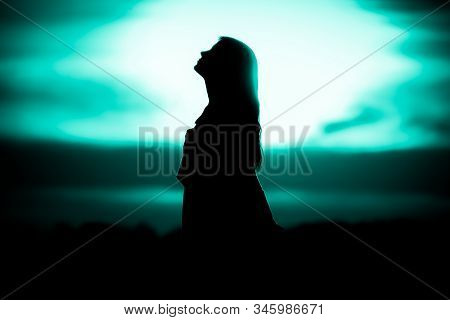 Youth Woman Soul At Turquoise Sun Meditation Dreaming Past Times. Silhouette In Front Of Sunset Or S