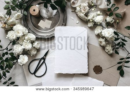 Moody Wedding Table Mockup Scene. Stationery Composition With Fading White Rose Flowers, Silver Plat