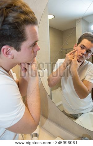 young caucasian man taking care of his face  looking at mirror reflection in bathroom morning clean